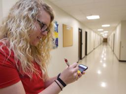 Courtney Schnell, a graduate assistant with Campus Recreation's wellness and nutrition team, writes down distance as she maps a walking path on the first floor of Nebraska Hall on Feb. 22.   Troy Fedderson, University Communications