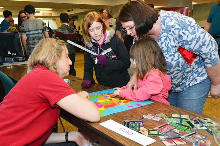 From left, Zoe Fischer, Emmalyn Smith, 3, and Vicki Cotton, all of Lincoln, participate in the How Well Do You Know Your World booth at the 16th annual Weatherfest and Central Plains Severe Weather Symposium on Saturday, April 16, 2016, at Hardin Hall on