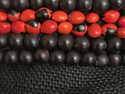 """Nenes""  and ""chumicos"" are nuts from Costa Rica that were beaded to embellish the garment ""Lo Que Fuimos"" ,  2017  (black&red) by Katherine Rodriguez Hernandez"