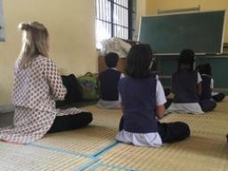 Anubhuti students help teach Jessica Fetrow proper yoga and meditation poses