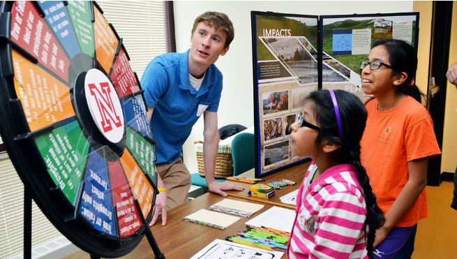 Claudia Carrillo (center) and Paula Carrillo (right) learn about drought from Jake Petr, a meteorology student in the Dept of Earth and Atmospheric Sciences, during the 16th annual Weatherfest in April 2016. The 2017 event is April 1.