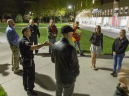 Capt. John Backer of the University Police Department (fourth from left) discusses lighting and landscaping improvements made to increase visibility on the plaza north of Love Library. The discussion was part of the university annual campus safety walk, w