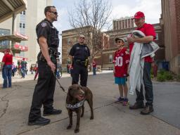 <em>Troy Fedderson | University Communication</em><br />K-9 handler Greg Byelick (left) discusses his new partner, Justice, with Mike Heller (right) and his son Robbie prior to the start of the Huskers' spring football game on April 15. The university was