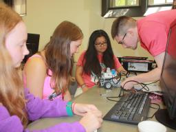 CSE students Mickey Tran and Tyler Barker help two Girl Scouts program a LEGO robot at this year's summer computing camp.