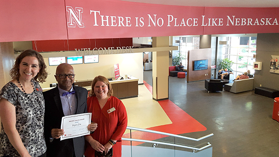 Rebecca Luhrs Baskerville (left), Nebraska director of education abroad, and Marnie Nelson (right), associate director, present Nutrition and Health Sciences assistant professor of practice Dipra Jha with a Smooth Sailing Award.