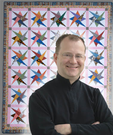 Jonathan Gregory, IQSCM Assistant Curator, and Haight quilt, in the pattern of Interlocking Triangles.
