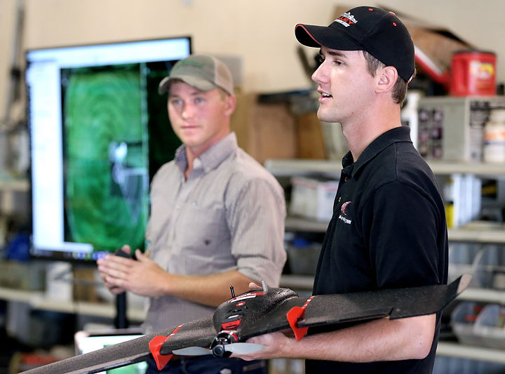 University of Nebraska–Lincoln graduate student and research technician John Parrish (left) listens as fellow UNL graduate student Joel Crowther talks about the eBee SQ drone he is holding during a Project SENSE demonstration Aug. 16. (Barrett Stinson)