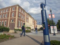 Students walk by the blue public safety phone on the south side of the Nebraska Union on Oct. 20. Due to technology advances and replacement costs, all but two of the phones are being removed from the university.   Troy Fedderson, University Communication