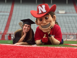 Abby Akin (left) celebrates graduation on August 14, 2017 with Nebraska Mascot Herbie Husker in Memorial Stadium. (Photo/Kyra Willats)