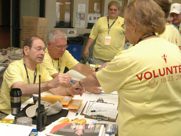 UNL's James Griesen (left), professor of educational administration, checks in volunteers at the Special Olympics Town in Pershing Center during the 2010 USA National Games.