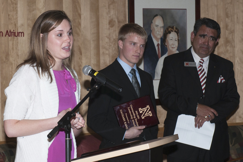 Jorden Mills accepts her award as Zachary Kane and Timothy Alvarez look on.