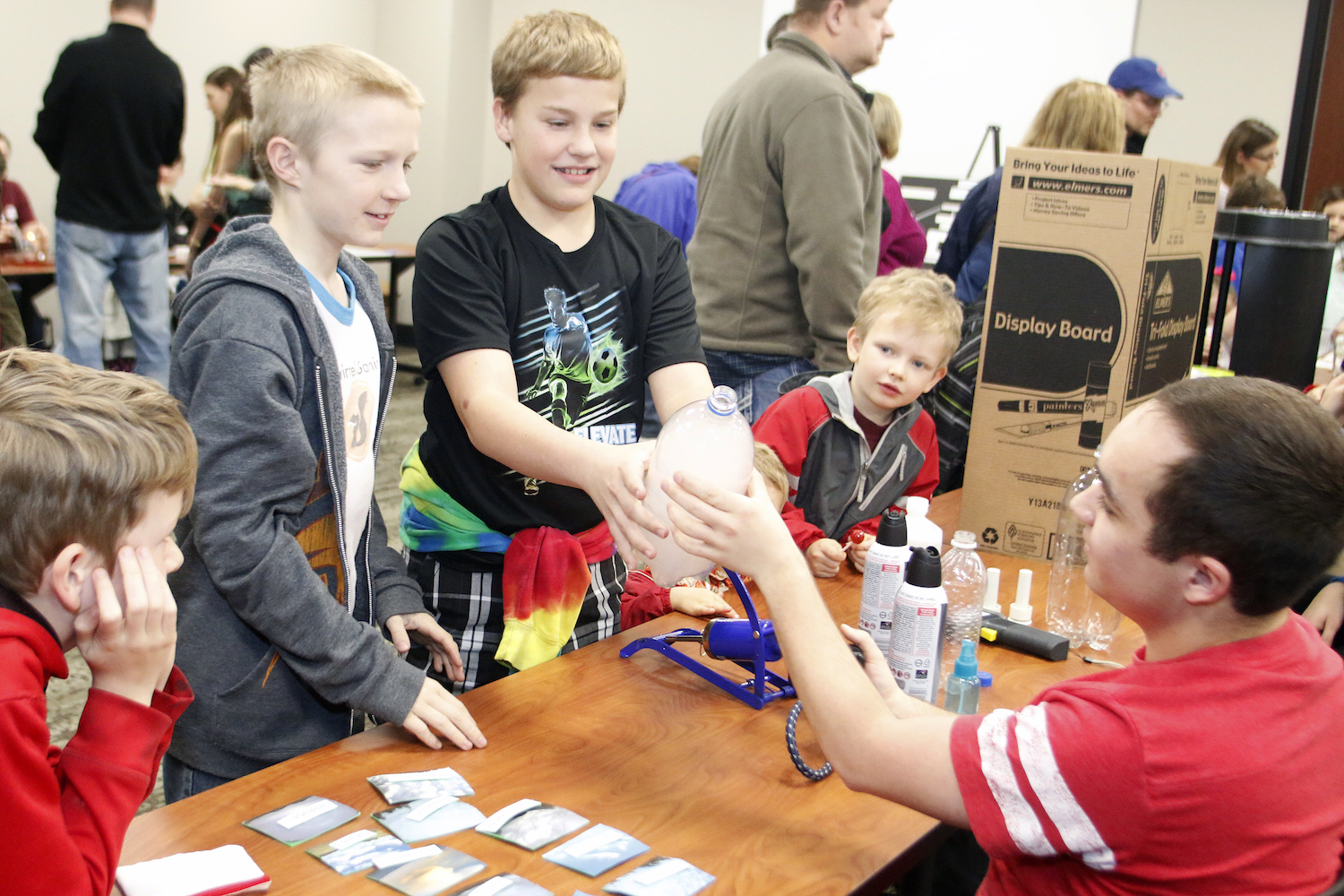 """Ryland Aksamit and Terry Glantz, both of Lincoln, push """"fog"""" out of a bottle during the 17th annual Weatherfest on Saturday, April 1, 2017, at Nebraska Innovation Campus. At right, Aiden Powers of Ceresco looks on. 