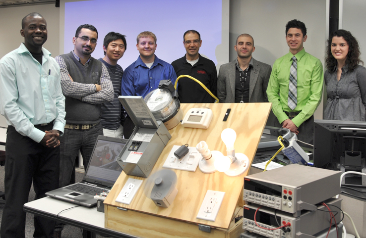 Members of Nebraska Engineering's I-SAVE team stand with their prototype energy monitoring device. Members (from left) are: Evans Sordiashie, Hosen Hasna, Xueyi Wang, Tim Wisnieski, Mahmoud Alahmad, Wisam Nader, Sean Bergstedt and Caitlin Brow.