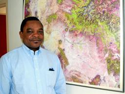 Koffi Djaman in front of satellite map