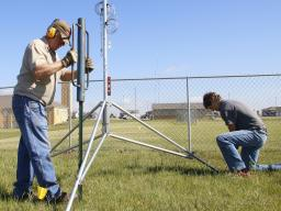 Glen Roebke, left, mesonet technician, and Regan Kerkman, NSCO student intern, install a weather station at St. Michael's Catholic Church property south of Lincoln in summer 2018.   Shawna Richter-Ryerson, Natural Resources