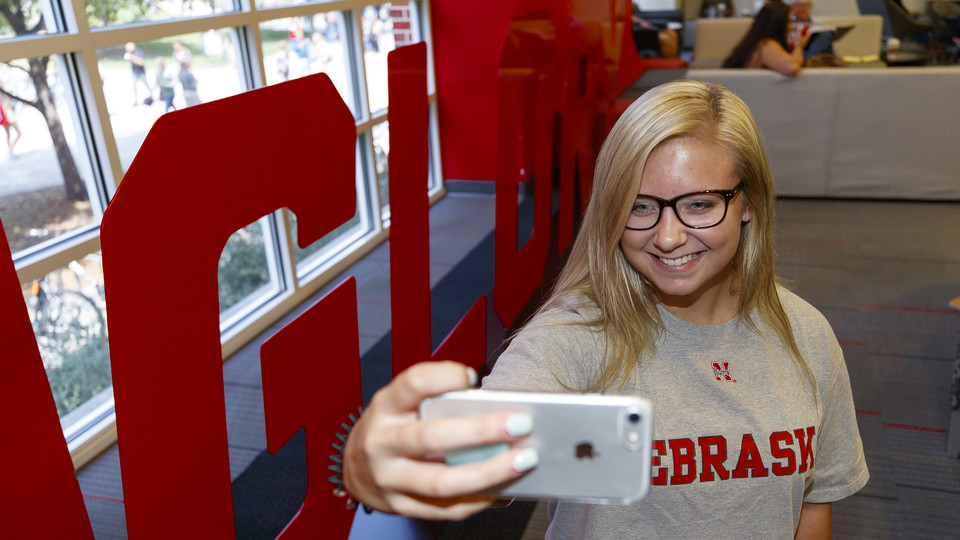 """Husker Alyssa Frederick takes a photo next to the """"Glory"""" sign in the Nebraska Union. The """"Grit"""" and """"Glory"""" signs, along with related sidewalk art and a website, appeared the week of Aug. 20.   Craig Chandler, University Communication"""