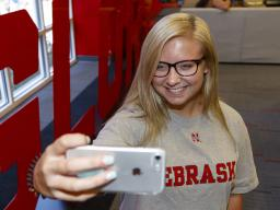 "Husker Alyssa Frederick takes a photo next to the ""Glory"" sign in the Nebraska Union. The ""Grit"" and ""Glory"" signs, along with related sidewalk art and a website, appeared the week of Aug. 20. 
